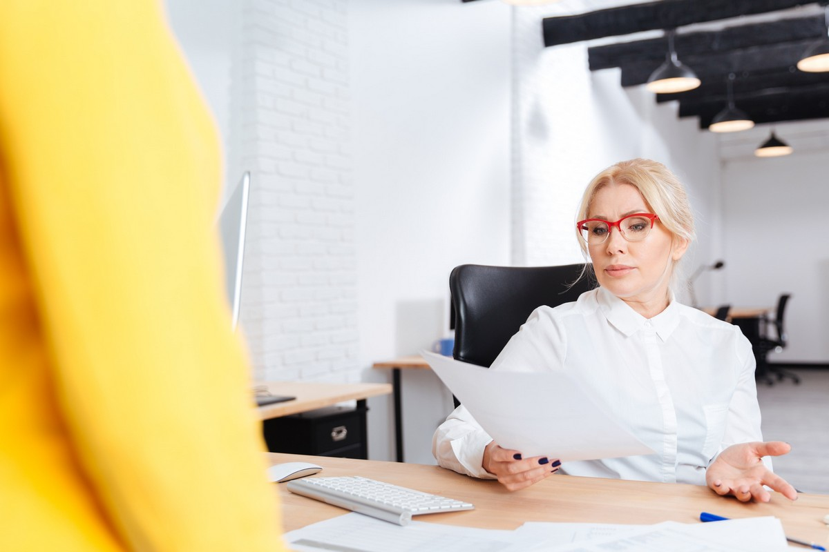 cheerful-beautiful-mature-businesswoman-interviewing-candidate-for-new-position-in-office
